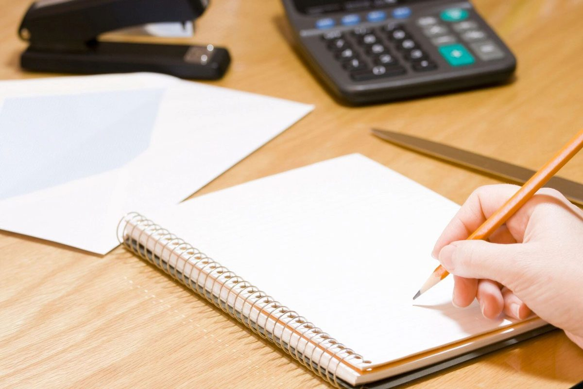 person writing on spiral notebook